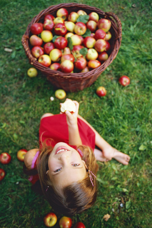 Playful portrait of a young girl eating an apple and looking up, overview