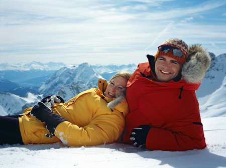 Couple laying in snow with mountains in background LANG_EVOIMAGES