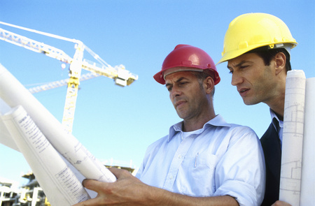 Construction worker and businessman looking at plans against blue sky