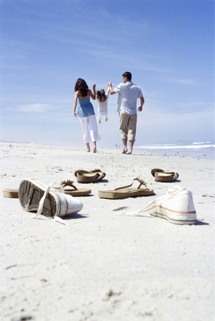 View of a pile of shoes on the beach with a family in the background