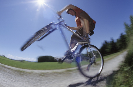 Underview, man balancing on the rear tire of his bike, blurred motion