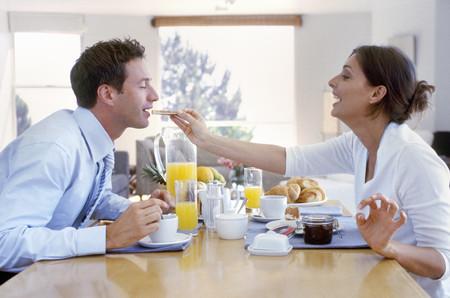 View of woman feeding her boyfriend breakfast
