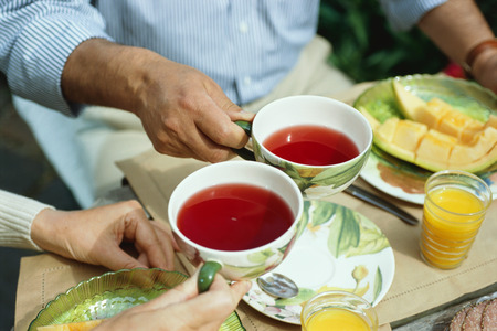 Overview of couple holding teacups and having breakfast