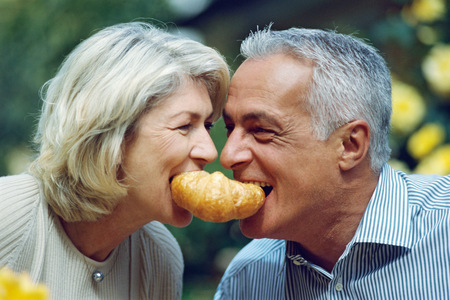 Mature couple playfully sharing a croissant LANG_EVOIMAGES