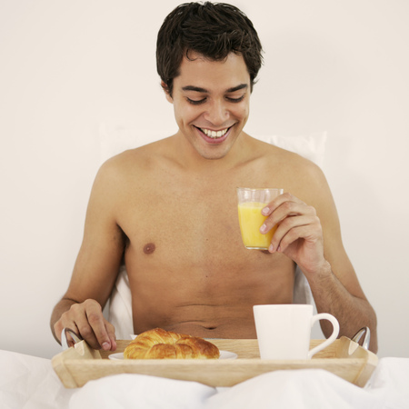 Portrait of a young man eating breakfast in bed