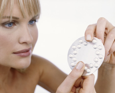 Studio shot of woman with birth control pills
