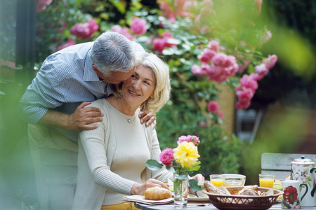 Mature man kissing seated woman at outdoor breakfast table, with selective focus