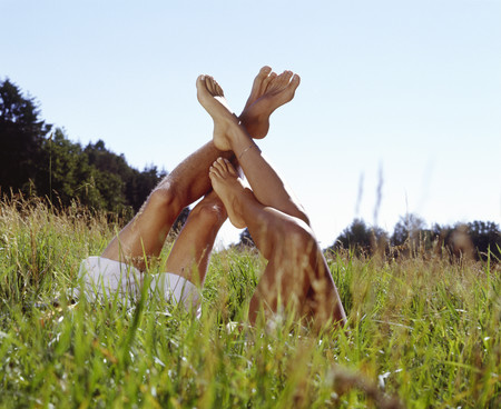View of a mans and womans legs sticking up out of tall grass