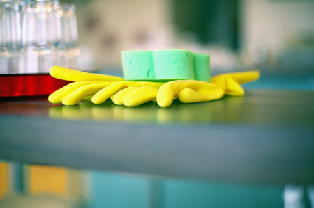 View of yellow rubber gloves and a green sponge LANG_EVOIMAGES