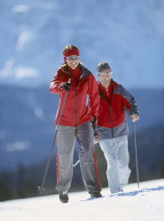 View of a young couple cross-country skiing in winter setting LANG_EVOIMAGES