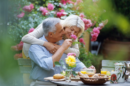 Mature couple embracing and having breakfast  with selective focus