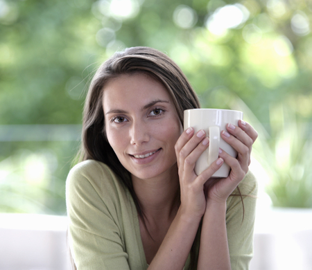 Portrait of a young woman holding a cup of coffee