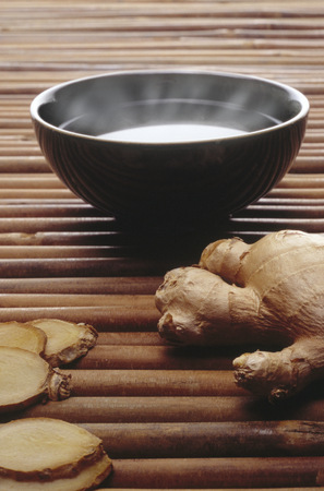 View of a bowl of steaming ginger tea beside ginger root