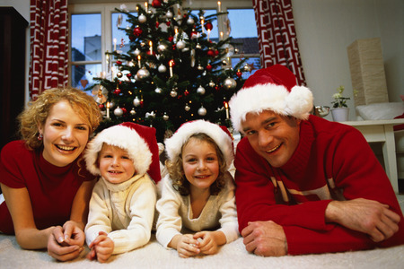Portrait of a family laying on the ground in Christmas attire