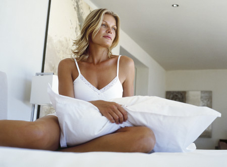 Portrait of a young woman holding a pillow LANG_EVOIMAGES