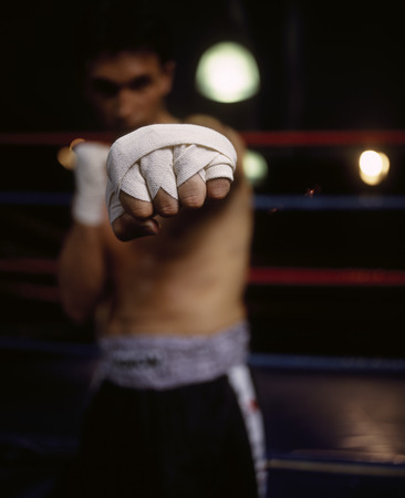 Portrait of a male boxer punching the camera