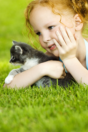 Young girl with kitten in grass LANG_EVOIMAGES