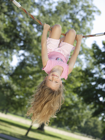 Girl hanging upside down on rope at playground