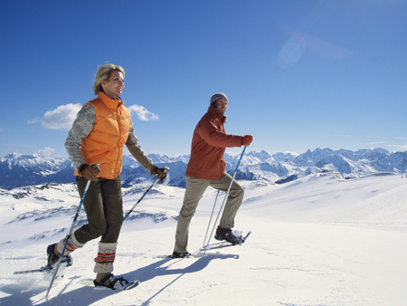 Couple snowshoeing with ski poles under blue sky LANG_EVOIMAGES