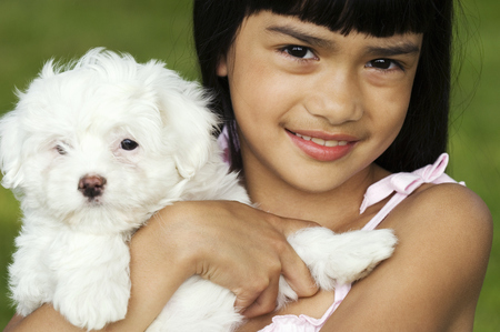 Young girl holding puppy outdoors LANG_EVOIMAGES