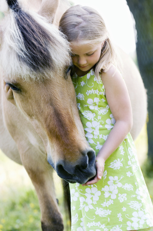 Young girl hugging horse outdoors