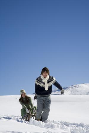 Man pulling girlfriend on sled, Luesener Alm, Dolomite Alps, South Tyrol, Italy