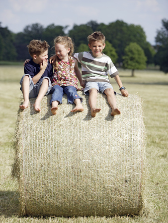 Young children sitting on hay bale outdoors