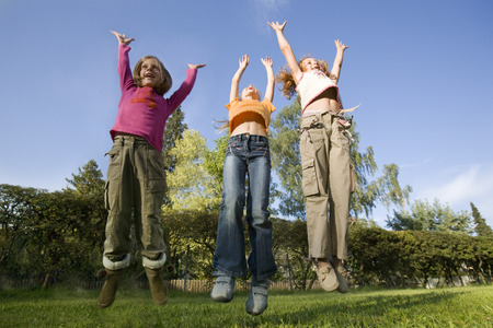 Three girls jumping with arms raised outdoors LANG_EVOIMAGES