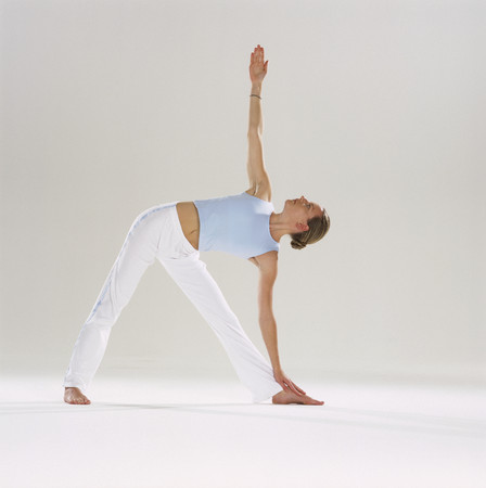 Woman doing yoga, leaning over and touching her foot
