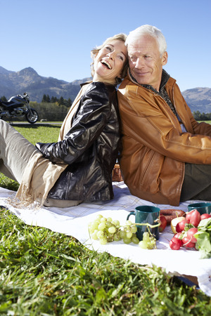 Senior couple having picnic with mountains in background LANG_EVOIMAGES
