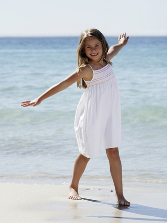 Girl with arms outstretched at beach
