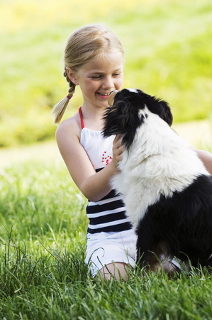 Young girl petting dog outdoors LANG_EVOIMAGES