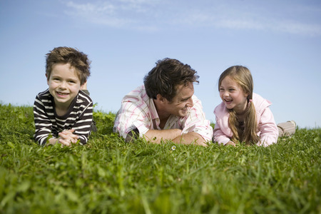 Father and children laying in grass LANG_EVOIMAGES