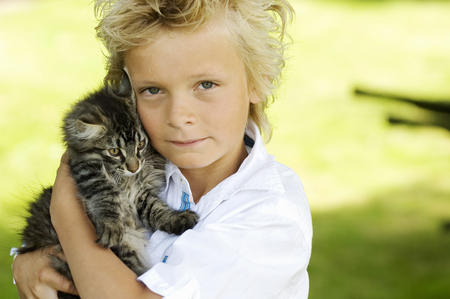 Young boy holding kitten outdoors