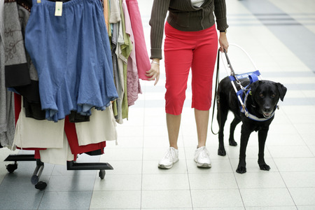 Blind woman and seeing eye dog shopping for clothing LANG_EVOIMAGES