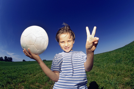 Young boy with ball flashing peace sign
