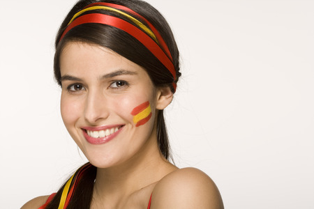 Young woman with Spanish flag painted on cheek