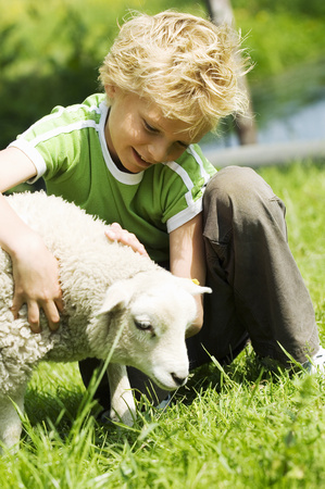 Young boy sitting in grass petting lamb