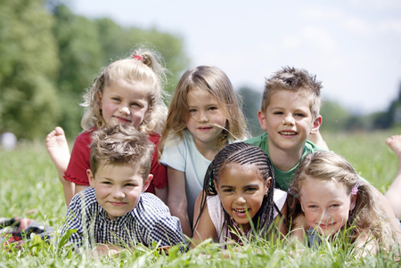 Group of young children laying in grass LANG_EVOIMAGES