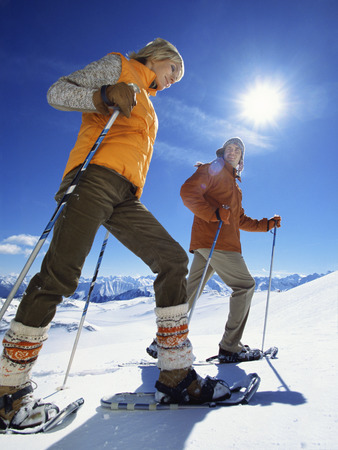 Low angle view of couple snowshoeing with ski poles LANG_EVOIMAGES