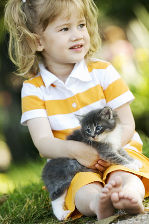 Young girl holding kitten outdoors LANG_EVOIMAGES
