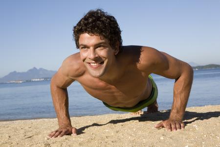Man doing push-ups on beach