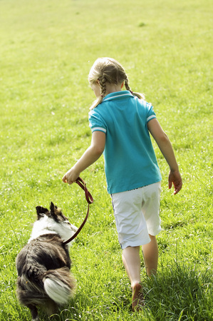 Rear view of girl walking dog in grass