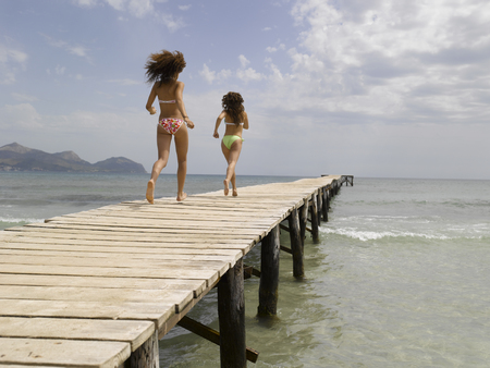 Two women running on pier LANG_EVOIMAGES