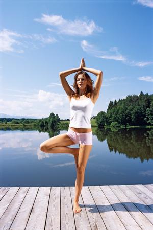Young woman doing yoga on dock
