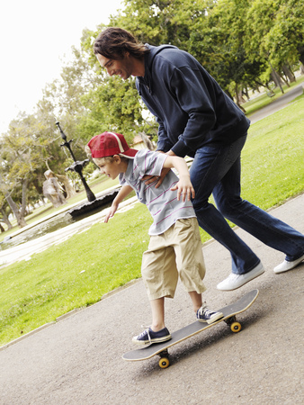 Father helping son skateboard