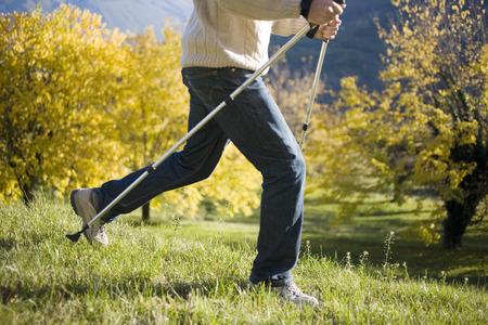 Man using Nordic walking poles in park