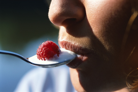 Woman eating yoghurt with raspberry