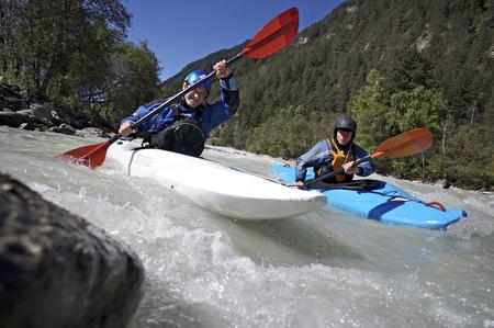 Two people paddling kayaks in whitewater
