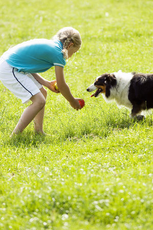 Young girl playing with dog in meadow